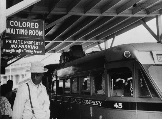 """Passengers under a sign that reads """"Colored Waiting Room"""" at a bus station in Durham,N.C., in1940"""